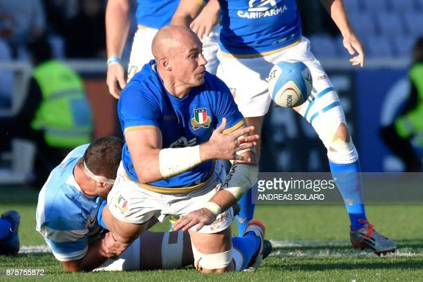 Italy's lock Sergio Parisse passes the ball despite the tackle of Argentina's second row Marcos Kremer during the International Rugby Union Test...
