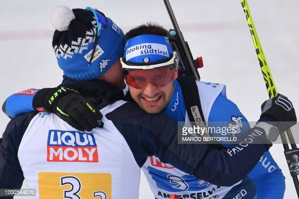 Italy's Lukas Hofer embraces teammate Italy's Dominik Windisch after Italy placed second of the IBU Biathlon World Cup 4x6 Mixed Relay in...