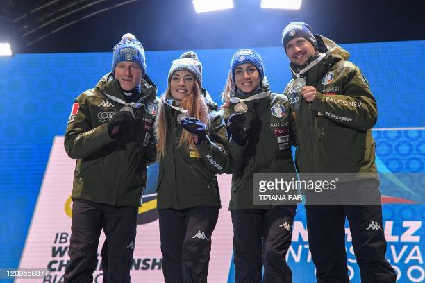Italy's Lukas Hofer, Italy's Dorothea Wierer, Italy's Lisa Vittozzi and Italy's Dominik Windisch pose with their silver on the podium after placing...