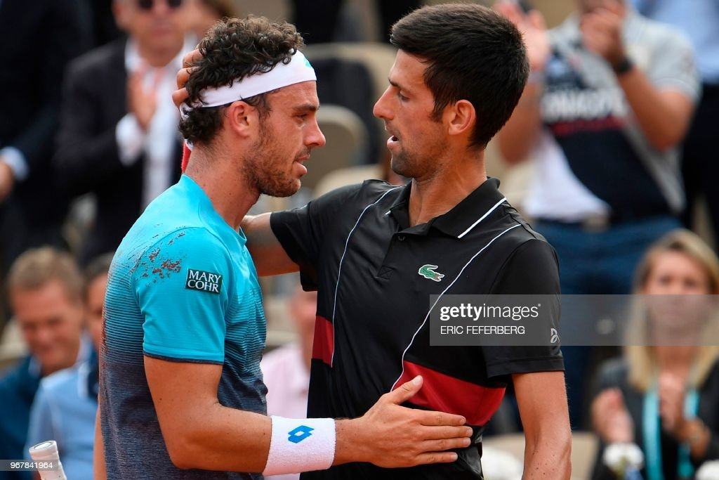TOPSHOT - Italy's Marco Cecchinato (L) embraces as he celebrates after victory over Serbia's Novak Djokovic in their men's singles quarter-final match on day ten of The Roland Garros 2018 French Open tennis tournament in Paris on June 5, 2018. - World number 72 Marco Cecchinato became the first Italian man in 40 years to reach a Grand Slam semi-final with a breathtaking 6-3, 7-6 (7/4), 1-6, 7-6 (13/11) epic victory over 12-time major winner Novak Djokovic.
