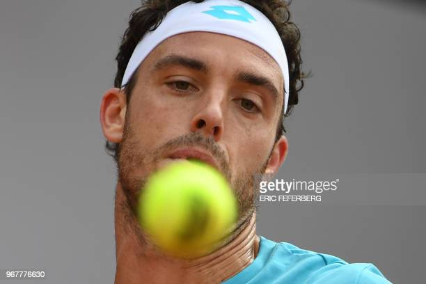 Italy's Marco Cecchinato eyes the ball as he returns the ball to Serbia's Novak Djokovic during their men's singles quarterfinal match on day ten of...