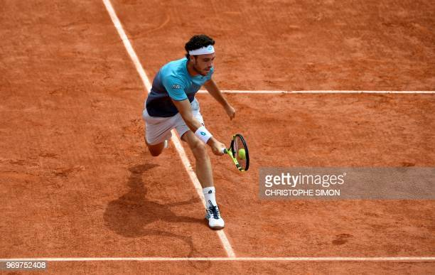 TOPSHOT Italy's Marco Cecchinato plays a forehand return to Austria's Dominic Thiem during their men's singles semifinal match on day thirteen of The...