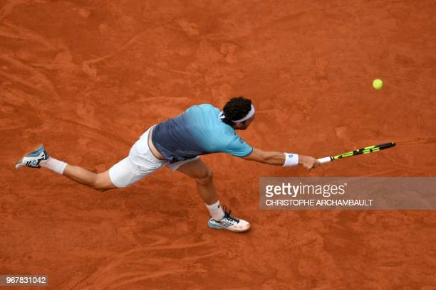 Italy's Marco Cecchinato plays a forehand return to Serbia's Novak Djokovic during their men's singles quarterfinal match on day ten of The Roland...