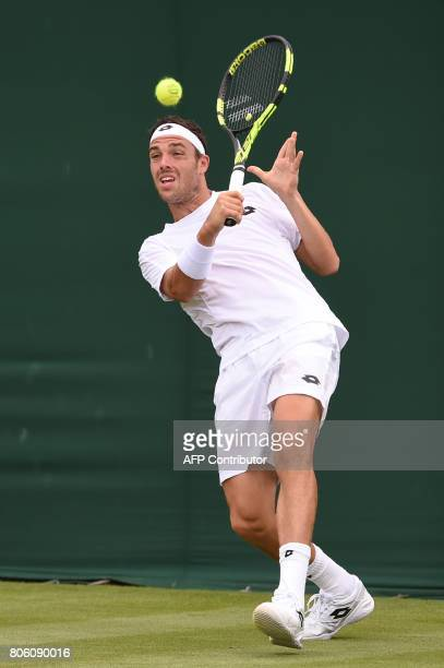Italy's Marco Cecchinato returns against Japan's Kei Nishikori during their men's singles first round match on the first day of the 2017 Wimbledon...