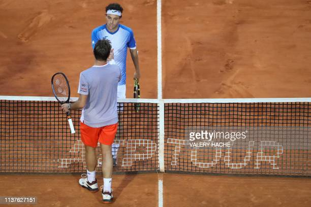 Italy's Marco Cecchinato shakes hands with Switzerland's Stan Wawrinka after winning during their tennis match on the day 4 of the Monte-Carlo ATP...