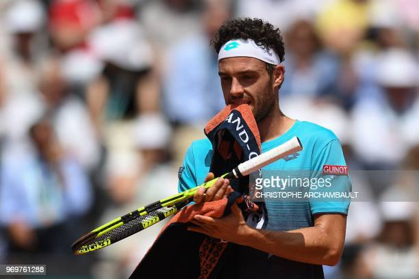 Italy's Marco Cecchinato uses his towel during his men's singles semifinal match against Austria's Dominic Thiem on day thirteen of The Roland Garros...