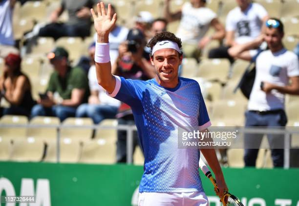 Italy's Marco Cecchinato waves at the audience as he celebrates after winning his tennis match against Bosnia Herzegovina's Damir Dzumhur on the day...