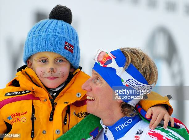 Italy's Marianna Longa celebrates with her son Michele after the10km Classic mass start women's event of the FIS World Cup Tour De Ski in Tesero on...