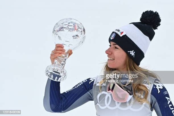 Italy's Marta Bassino celebrates with the Overall Cristal Globe of the FIS Alpine Ski World Cup for the Women's Giant Slalom after competing in the...