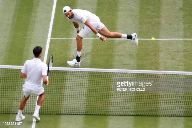 Italy's Matteo Berrettini returns against Serbia's Novak Djokovic during their men's singles final match on the thirteenth day of the 2021 Wimbledon...