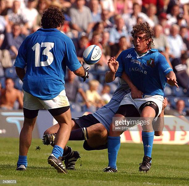 Italy's Mauro Bergamasco passes to Andrea Masi as he is tackled by Scotland's Jason White during their World Cup warm up match at Murrayfield Stadium...