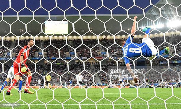 Italy's midfielder Alessandro Florenzi deflects the ball from the goal as Italy's goalkeeper Gianluigi Buffon looks on during the Euro 2016...