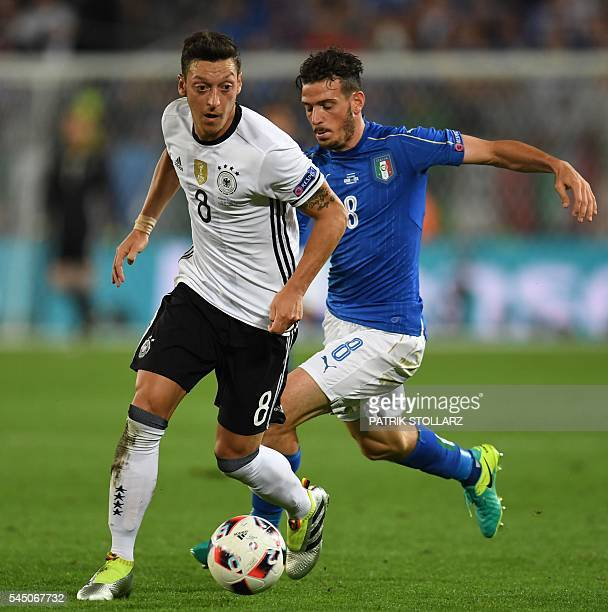 Italy's midfielder Alessandro Florenzi vies for the ball with Germany's midfielder Mesut Oezil during the Euro 2016 quarterfinal football match...