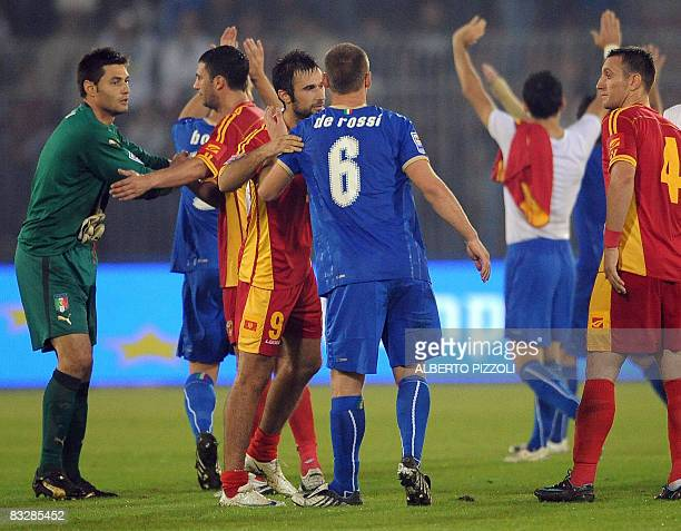 Italy's midfielder Daniele De Rossi and Montenegro's forward Mirko Vucinic who both play at AS Roma embrace themselves at the end of their national...