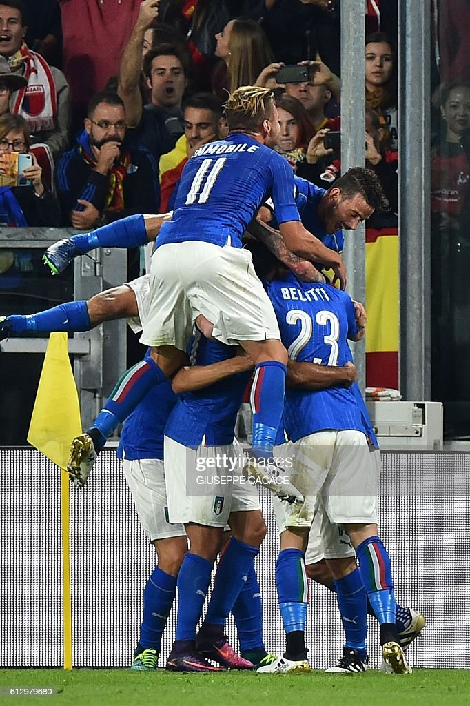 Italy's midfielder Daniele De Rossi (hidden) celebrates with teammates Italy's forward Andrea Belotti (R), Italy's midfielder Riccardo Montolivo, Italy's defender Leonardo Bonucci, Italy's midfielder Alessandro Florenzi and Italy's forward Ciro Immobile (L) after scoring a penalty against Spain's goalkeeper David de Gea during the WC 2018 football qualification match between Italy and Spain on October 6, 2016 at the Juventus stadium in Turin / AFP / GIUSEPPE