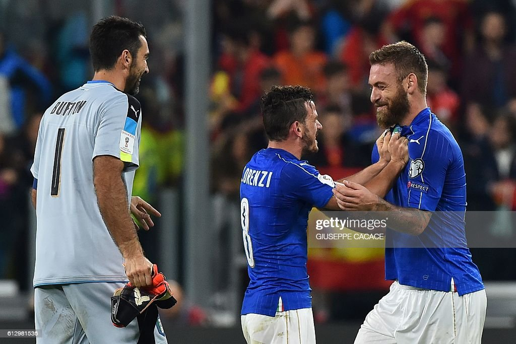 Italy's midfielder Daniele De Rossi (R) celebrates with teammates Italy's midfielder Alessandro Florenzi and Italy's goalkeeper Gianluigi Buffon (L) at the end of the WC 2018 football qualification match between Italy and Spain on October 6, 2016 at the Juventus stadium in Turin. The match ended on a 1-1 draw. / AFP / GIUSEPPE