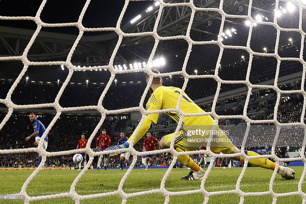 Italy's midfielder Daniele De Rossi scores a penalty against Spain's goalkeeper David de Gea during the WC 2018 football qualification match between Italy and Spain on October 6, 2016 at the Juventus stadium in Turin. The match ended on a 1-1 draw. / AFP / Marco BERTORELLO