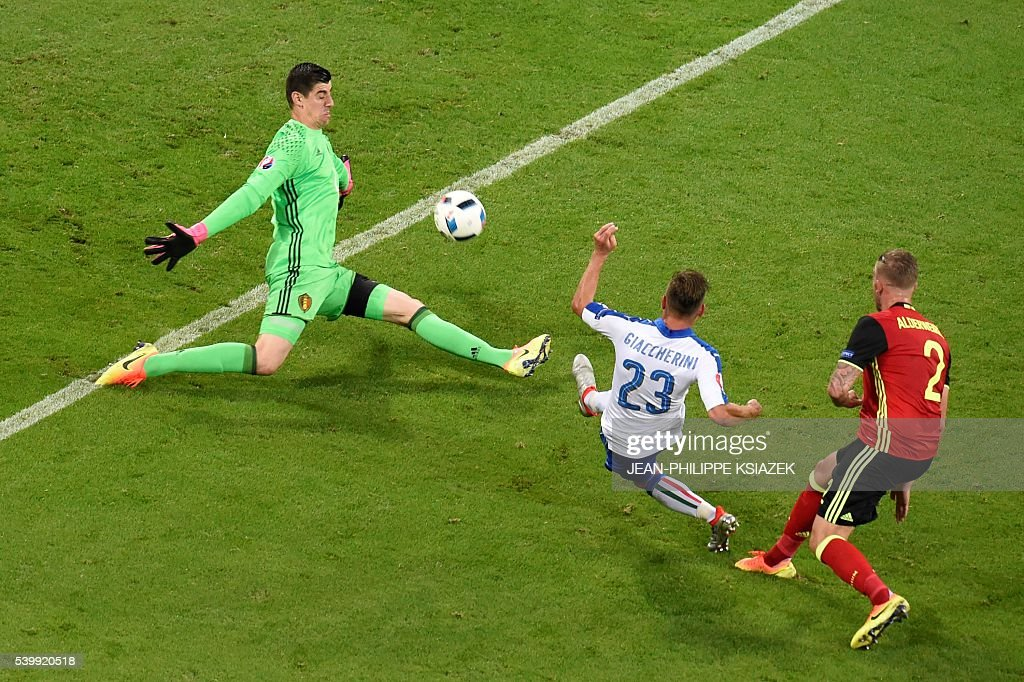 TOPSHOT - Italy's midfielder Emanuele Giaccherini shoots the team's first goal past Belgium's goalkeeper Thibaut Courtois during the Euro 2016 group E football match between Belgium and Italy at the Parc Olympique Lyonnais stadium in Lyon on June 13, 2016. / AFP / JEAN