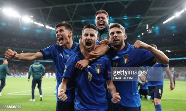 Italy's midfielder Jorginho celebrates with teammates after scoring in a penalty shootout and winning the UEFA EURO 2020 semi-final football match...