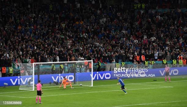 Italy's midfielder Jorginho shoots and scores past Spain's goalkeeper Unai Simon in a penalty shootout during the UEFA EURO 2020 semi-final football...
