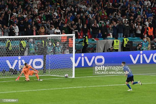 Italy's midfielder Jorginho shoots and scores the winning goal past Spain's goalkeeper Unai Simon in a penalty shootout during the UEFA EURO 2020...