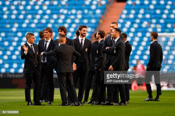 Italy's midfielder Marco Verratti chats with Italy's defender Davide Astori and teammates as they gather on the pitch before the World Cup 2018...