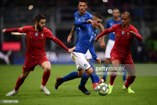 Italy's midfielder Marco Verratti makes his wau through Portugal's midfielder Bernardo Silva and Portugal's midfielder Joao Mario during the UEFA...