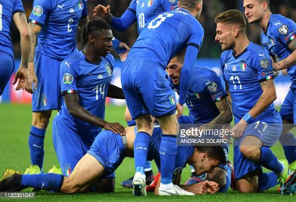 Italy's midfielder Nicolo Barella celebrates with teammates Moise Kean and Ciro Immobile after scoring during the Euro 2020 Group J qualifying...