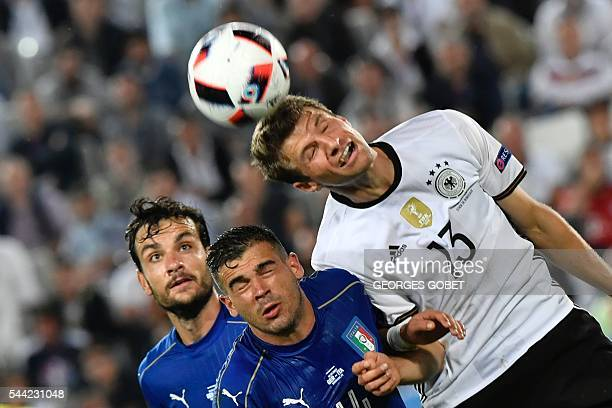 Italy's midfielder Stefano Sturaro and Germany's midfielder Thomas Mueller jump for the ball during the Euro 2016 quarter-final football match...