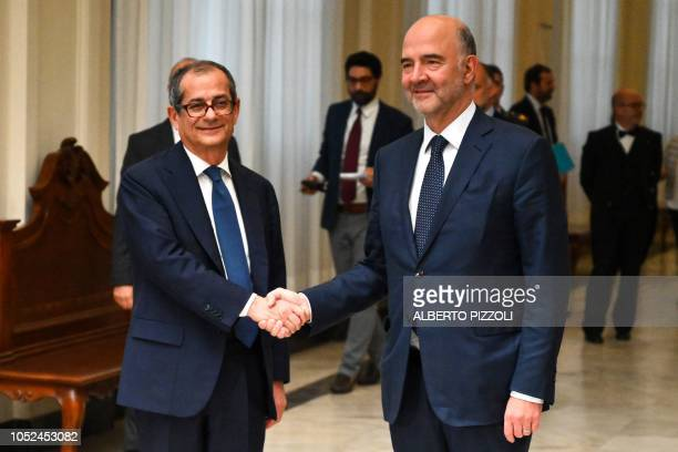 Italy's Minister of Economy and Finances Giovanni Tria and European Affairs Commissioner Pierre Moscovici shake hands within their meeting at the...