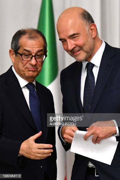 Italy's Minister of Economy and Finances Giovanni Tria and European Affairs Commissioner Pierre Moscovici talk during a press conference following...