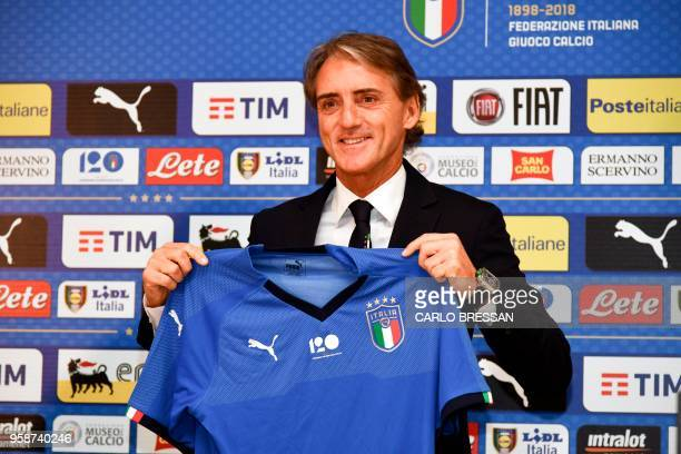 Italy's national football team newly appointed head coach, Roberto Mancini holds Italy's jersey during a press conference on May 15, 2018 at the...