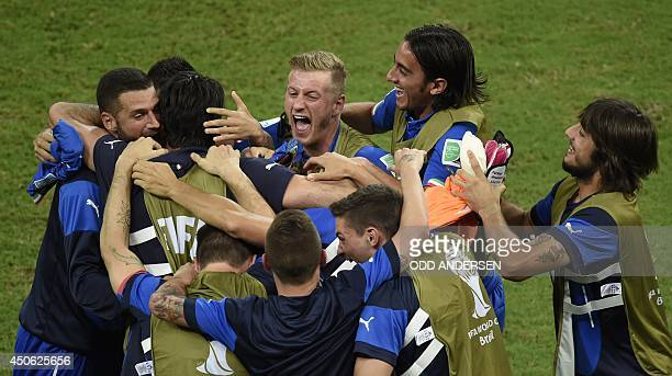 Italy's national football team players celebrate at the end of a Group D football match between England and Italy at the Amazonia Arena in Manaus...