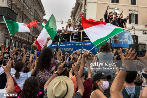 Italy's national men's football team celebrate with Italian fans during an open-top bus victory parade in the streets of Rome following a meeting...