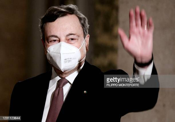 Italy's new prime minister, former European Central Bank President Mario Draghi waves as he leaves on February 12, 2021 the Quirinale palace...