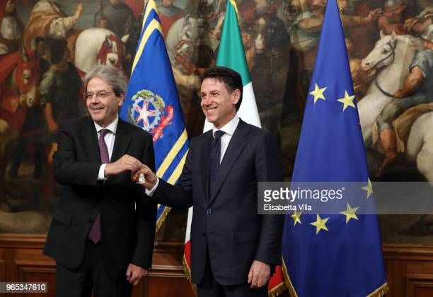 Italy's new Prime Minister Giuseppe Conte rings the bell which he received from outgoing Prime Minister Paolo Gentiloni marking the moment he takes...