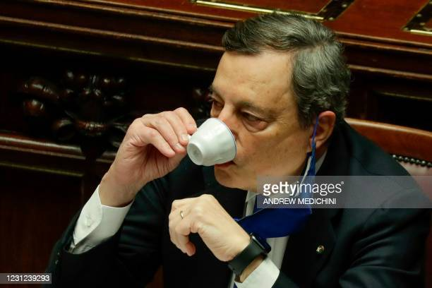 Italy's new Prime Minister Mario Draghi drinks a coffee as he attends a lower Chamber session in the Italian Parliament on February 18, 2021 in Rome,...