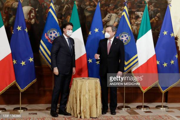 Italy's new Prime Minister Mario Draghi holds the cabinet minister bell as Italian outgoing Prime Minister Giuseppe Conte looks on, during a handover...