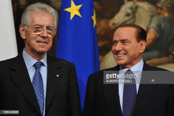 Italy's new Prime Minister Mario Monti poses with outgoing Prime Minister Silvio Berlusconi as Monti takes office on November 16, 2011 at Palazzo...