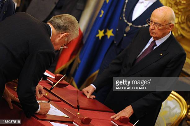 Italy's new Prime Minister Mario Monti signs in front of President Giuli Napolitano during the swearingin ceremony of the new Italian government on...