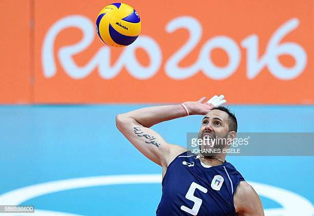 Italy's Osmany Juantorena spikes the ball during the men's qualifying volleyball match between France and Italy at the Maracanazinho stadium in Rio...
