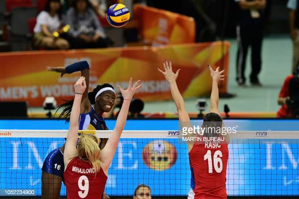 Italy's Paola Egonu spikes the ball against Serbia's Brankica Mihajlovic and Milena Rasic during the 2018 FIVB World Championship volleyball women's...