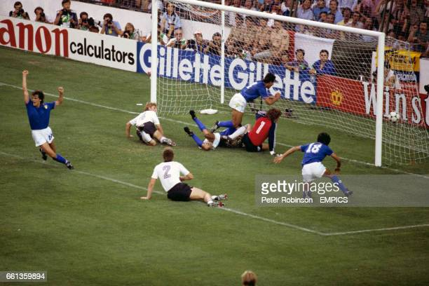 Italy's Paolo Rossi forces the ball past West Germany goalkeeper Harald Schumacher to score the opening goal with teammate Antonio Cabrini in close...