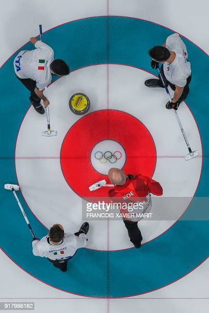 Italy's players Amos Mosaner Simone Gonin and Joel Retornaz follow their stone as Canada's Kevin Koe looks on during the curling men's round robin...