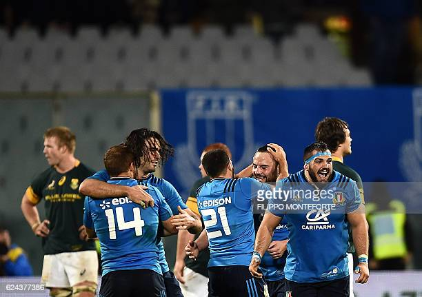 Italy's players celebrate after winning the rugby union Test match between Italy and South Africa at the Artmio Franchi Stadium in Florence on...