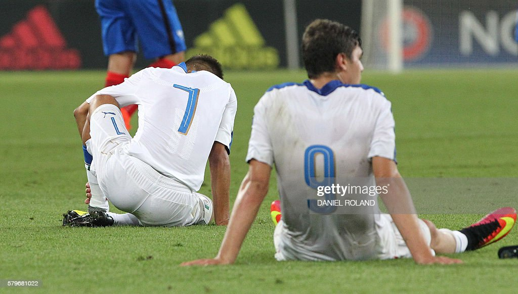 Italy's players sit on the pitch after the 4-0 loss in the Under 19 Football European Championships final match France vs Italy in Sinsheim, southern Germany, on July 24, 2016. / AFP / DANIEL