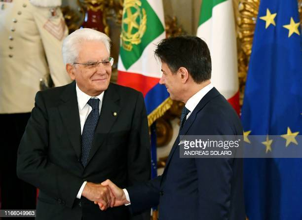 Italy's President Sergio Mattarella and Italy's Prime Minister Giuseppe Conte shake hands during a swearing-in ceremony at the Quirinale presidential...