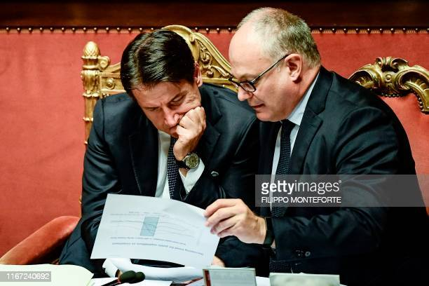 Italy's Prime Minister Giuseppe Conte and Italy's Finance and Economy Minister Roberto Gualtieri go through documents as they wait while the new...