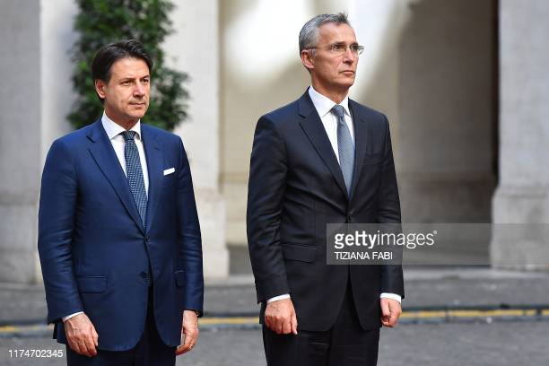 Italy's Prime Minister Giuseppe Conte and NATO Secretary General Norway's Jens Stoltenberg stand at attention during a welcoming ceremony upon...