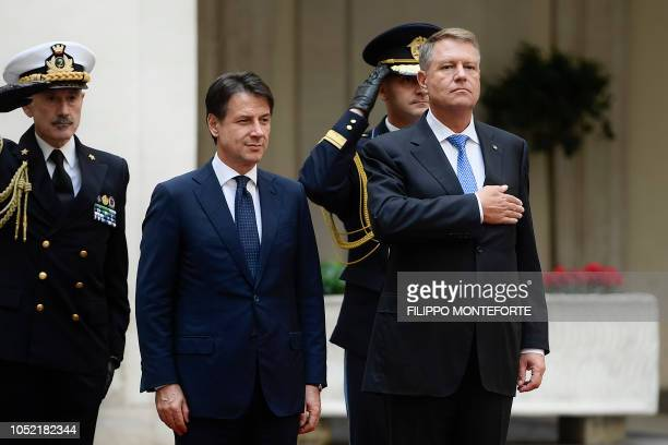 Italy's prime minister Giuseppe Conte and Romania's President Klaus Iohannis stand at attention during a welcoming ceremony upon Iohannis' arrival...